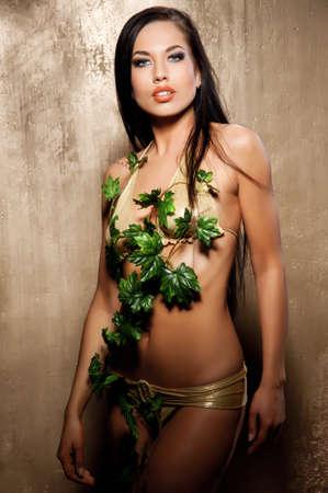 Beautiful woman in bikini with tropical leaves photo