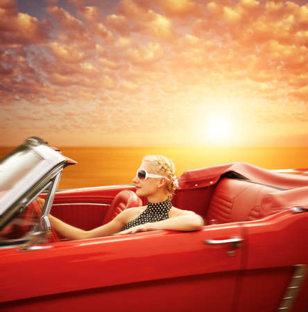 Woman Driving Retro-Auto gegen schönen Himmel.