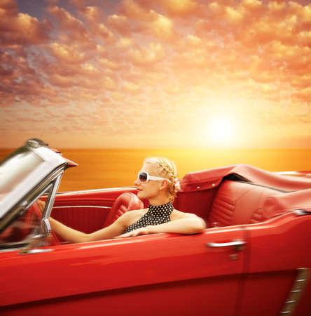 car model: Woman driving retro car against beautiful sky. Stock Photo