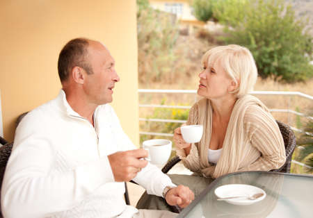 women coffee: Middle-aged couple drinking coffee outdoors Stock Photo