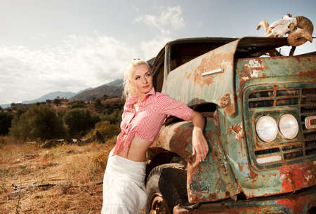 old truck: Attractive blond woman near an old truck.