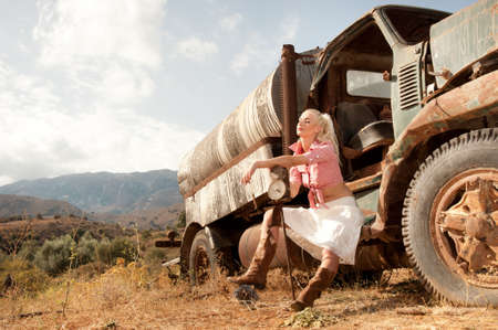 Attractive blond woman near an old truck. photo