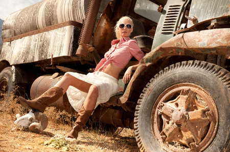 crashed: Attractive blond woman near an old truck.