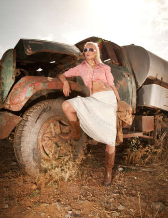 abandoned car: Attractive blond woman near an old truck.