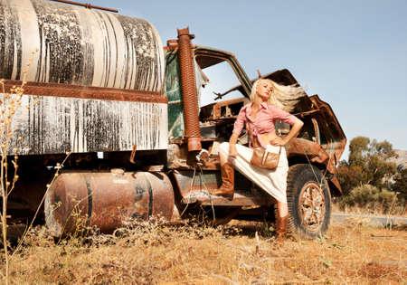 Attraktive blonde Frau in der Nähe einer alten LKW.