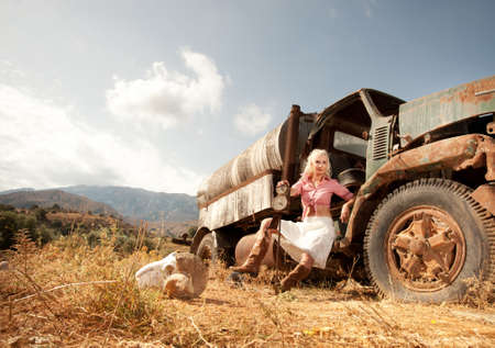 old cowboy: Attractive blond woman near an old truck.