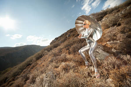 Cyber woman witu umbrella in a mountains. photo