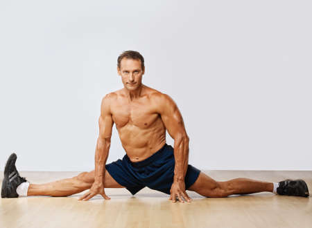 Handsome muscular man doing the splits. Stock Photo - 10199621