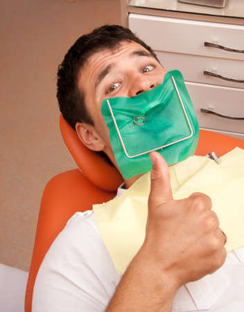 hand on mouth: Happy man at the dentists surgery.