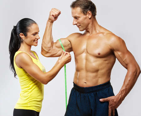 abdominals: Woman measuring athletics man biceps.