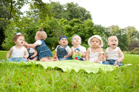 babies with toys: Group of babies outdoors.