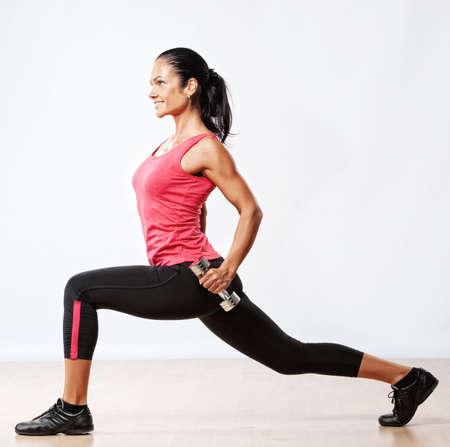 levantando pesas: Mujer atleta hermoso ejercicio en el gimnasio.