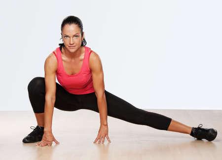 en cuclillas: Mujer bella atleta haciendo ejercicio de gimnasio.