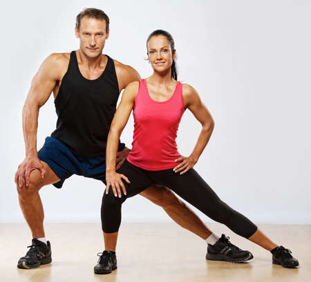 Athletic man and woman doing fitness exercise photo