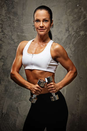 leisure centre: Beautiful athlete woman  with dumbbells. Stock Photo