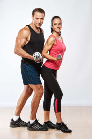 Athletic man and woman with a dumbells. Stock Photo