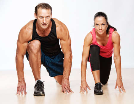 athletic activity: Athletic man and woman doing fitness exercise