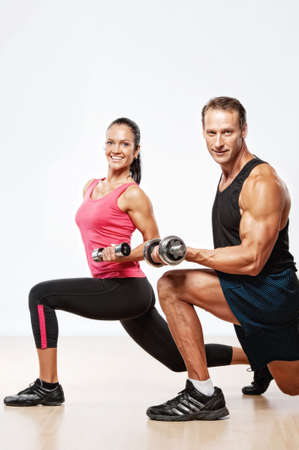 athletic activity: Athletic man and woman with a dumbells. Stock Photo