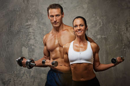 fitness couple: Athletic man and woman with a dumbells. Stock Photo