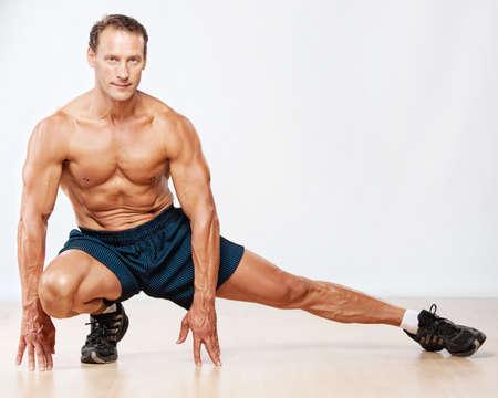 stretching: Hermoso hombre musculoso haciendo ejercicios de estiramiento. Foto de archivo