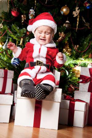 niño llorando: El llanto niño con cajas de regalo Foto de archivo