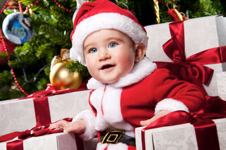 Little Santa boy with gift boxes. photo