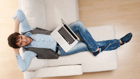 Young man with a laptop lying on a sofa. photo