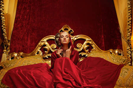 Beautiful woman with a carnival mask sitting in bed photo
