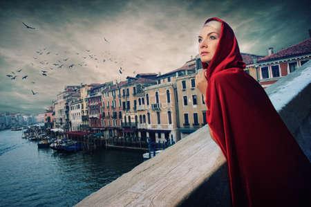 Beautifiul woman in red cloak on a bridge. photo