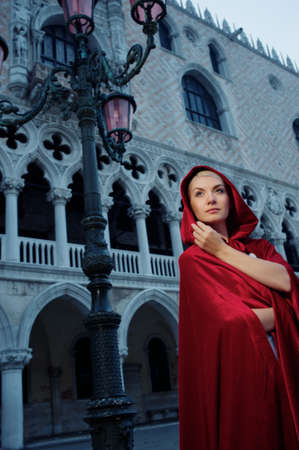 Beautifiul woman in red cloak against Dodges Palace photo