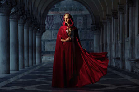 mystery woman: Beautifiul woman in red cloak outdoors