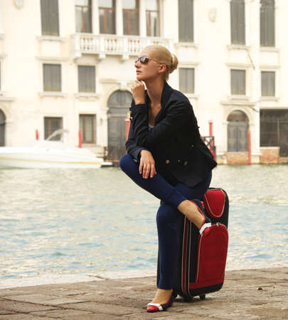 Blond woman sitting on a suitcase photo