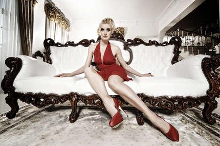 Beautiful lady sitting on a luxury sofa. photo
