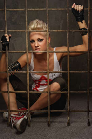 Punk girl behind bars photo
