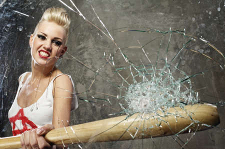 punk: Punk girl breaking glass with a bat Stock Photo