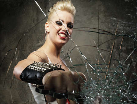 Punk girl breaking glass with a brass knuckles photo