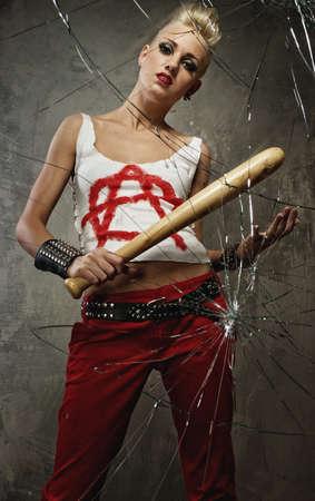Punk girl with a bat behind broken glass photo