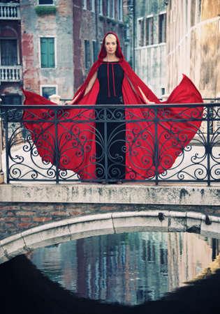 Beautifiul woman in red cloak on a bridge.