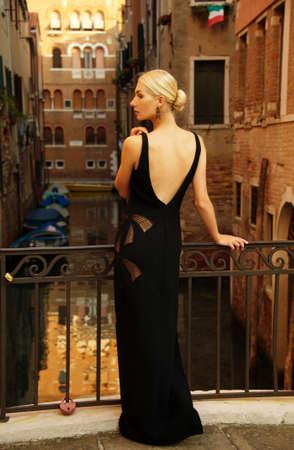 Beautifiul woman in black dress on a bridge photo