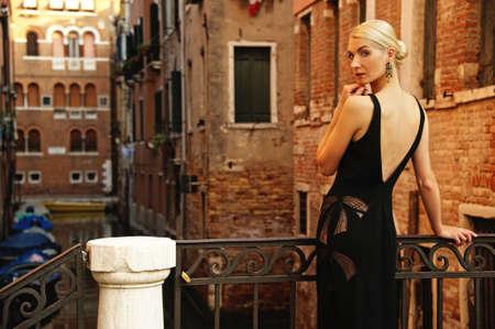black dress: Beautifiul woman in black dress on a bridge Stock Photo