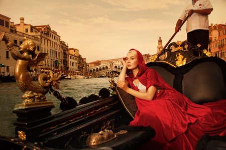 Beautifiul vrouw in rode mantel rijden op gandola Stockfoto