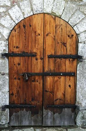 door bolt: Puerta antigua de madera en una pared de piedra. Foto de archivo