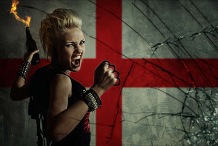 anarchy: Punk girl with Molotov cockatail against England flag. Stock Photo