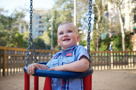 Cute baby on a swing in a park photo