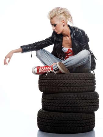 Punk girl sitting on tires.