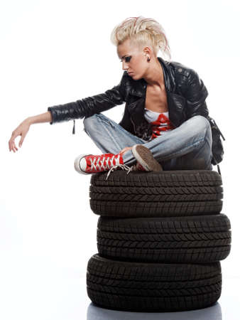 Punk girl sitting on tires. photo