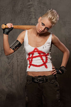 s horn: Punk girl with a baseball bat against grey background.