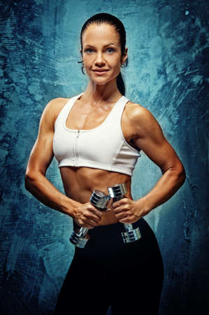 vertical wellness: Beautiful athlete woman  with dumbbells. Stock Photo