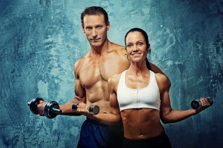 Athletic man and woman with a dumbells. photo