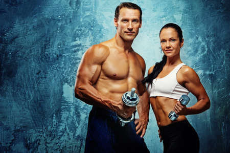 Athletic man and woman with a dumbells. Stock Photo - 11232096